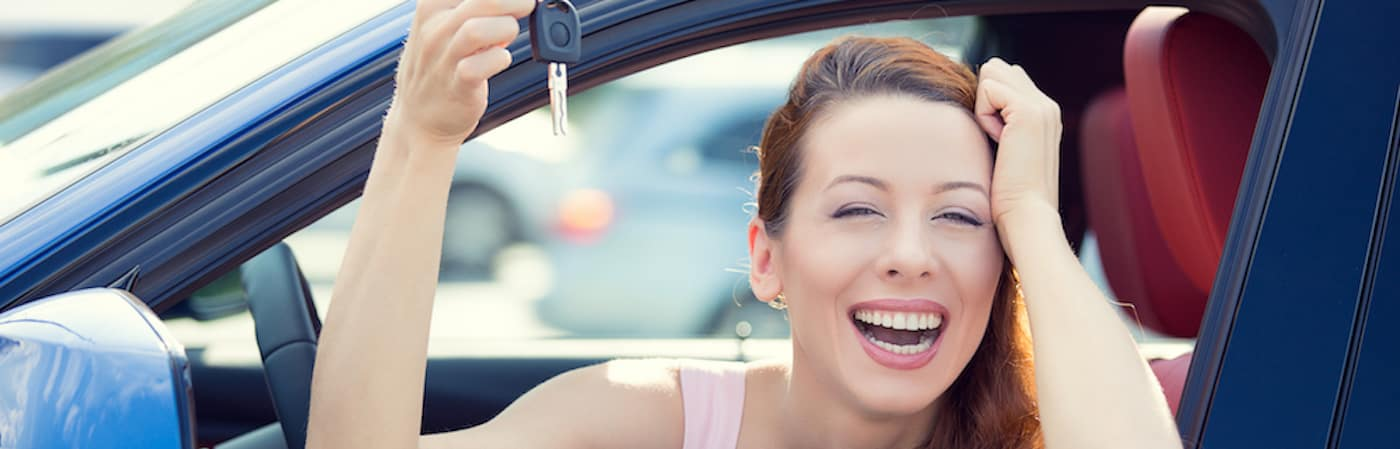 Smiling woman holding car keys while sitting in drivers seat