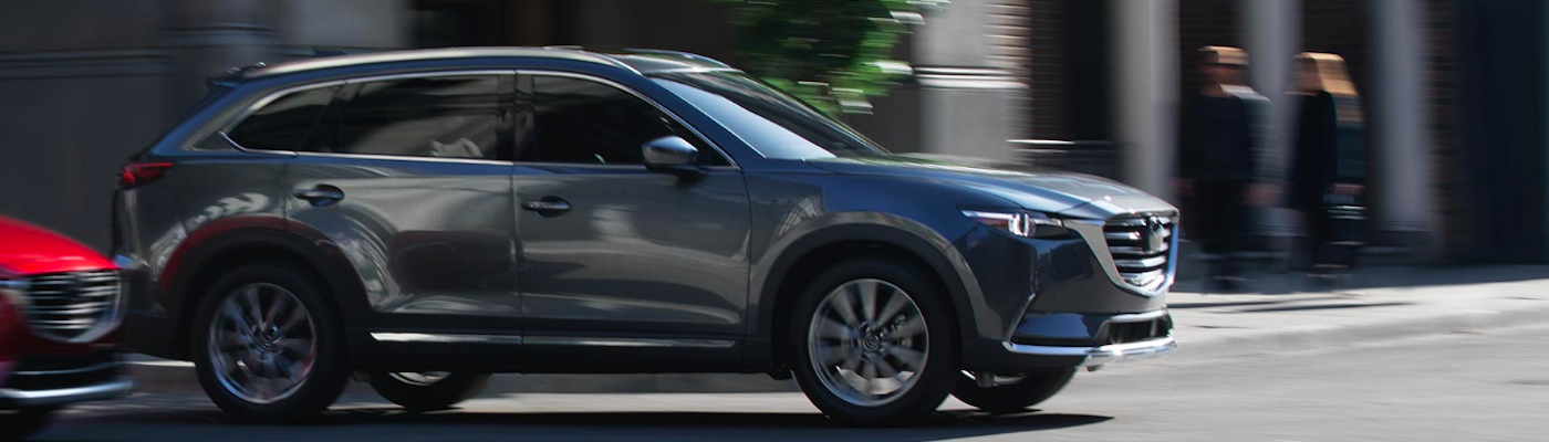 Mazda CX-9 driving through intersection on busy city street
