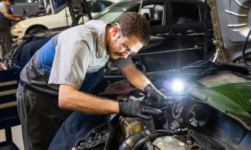 technician working in under car hood