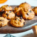Pumpkin chocolate chip cookies on a wooden serving board.
