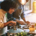 A woman adding seasoning to a pot and a man chopping vegetables for a family dinner