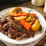 Pot roast, carrots, potatoes, and thyme on a white plate with a dotted rim.