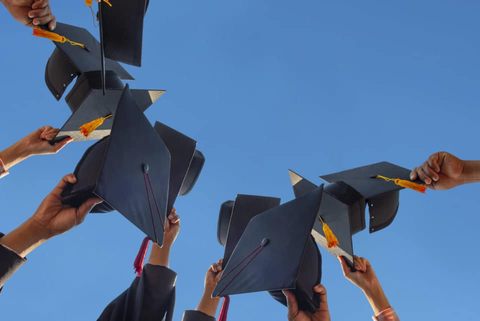 students tossing graduation caps into sky