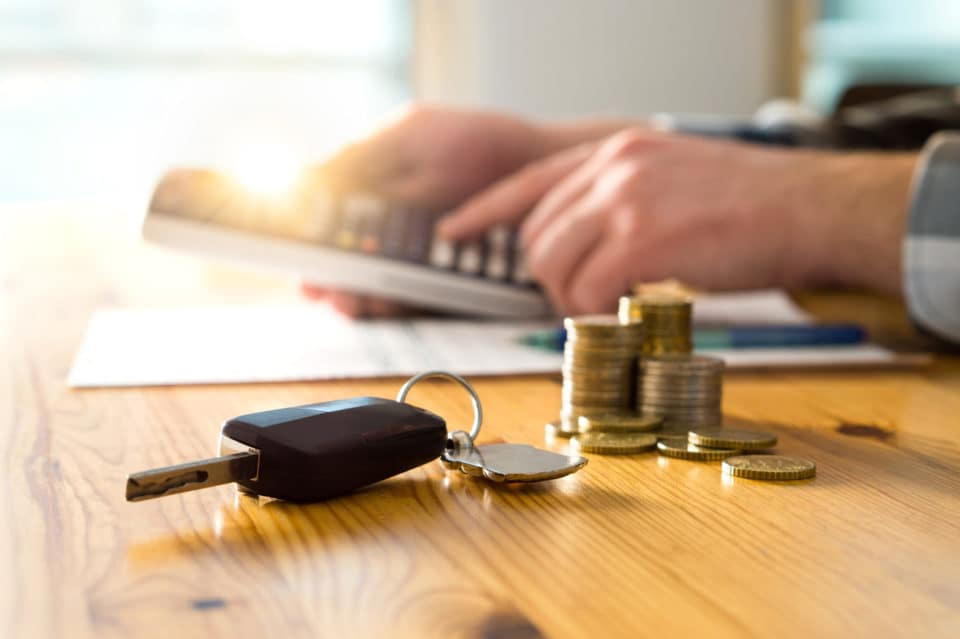 Car keys and money on table with man using calculator