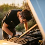 Young man looking under the hood of his vehicle