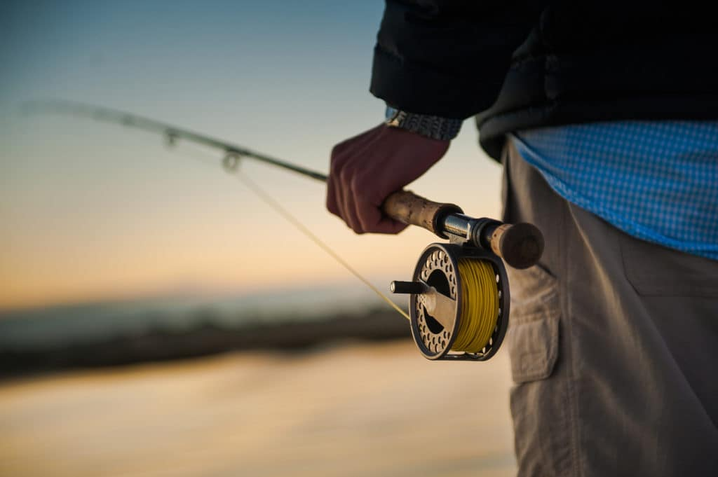 Sunrise over the water with man holding a fly rod and reel