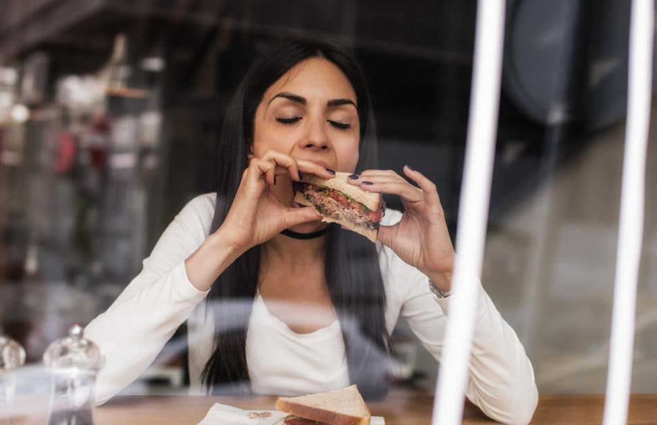 Beautiful smiling young woman eating sandwich in cafe.